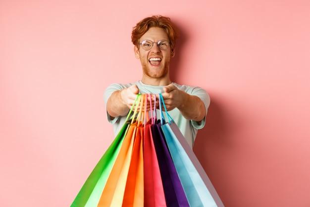 Szczęśliwy rudy mężczyzna wyciągnąć ręce z torby na zakupy, daje prezenty, stojąc na różowym tle.