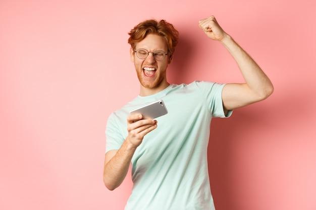 Szczęśliwy rudy mężczyzna wygrywający w mobilnej grze wideo, podnoszący rękę i krzyczący z radości tak, świętujący zwycięstwo, patrząc na smartfona, stojący na różowym tle.