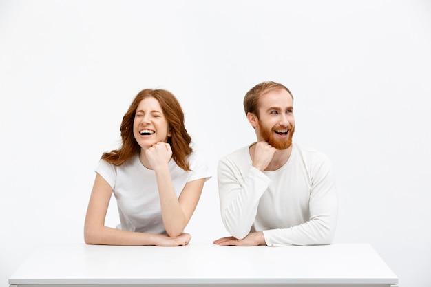 Szczęśliwy rudzielec mężczyzna i kobieta śmia się przy stołem
