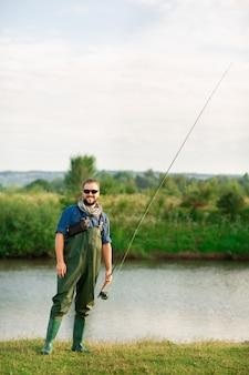 Szczęśliwy rybak ze specjalnym garniturem i wędką w pobliżu rzeki