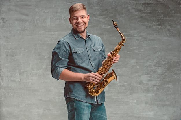 Szczęśliwy saksofonista z saksofonem na szarej przestrzeni