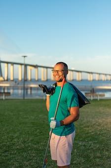 Szczęśliwy samiec wolontariusz pozuje w miasto parku