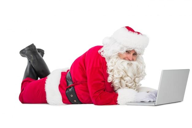 Szczęśliwy santa lying on the beach i używać laptop