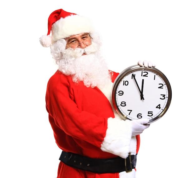 Szczęśliwy santa w okularach, wskazując na zegar wskazujący pięć minut do bożego narodzenia