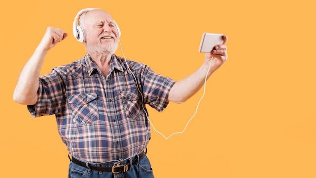 Szczęśliwy senior ogląda teledyski na telefonie