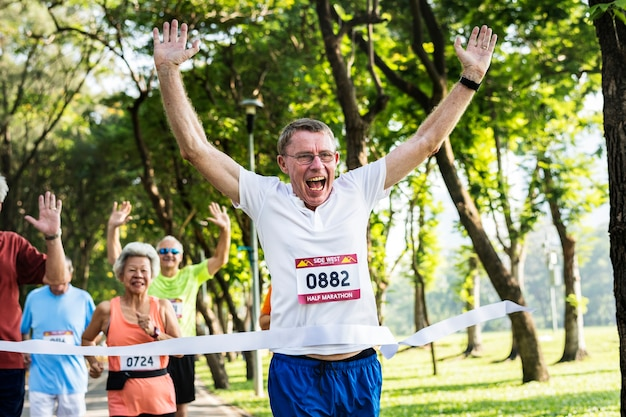 Szczęśliwy senior przebiegający przez linię mety