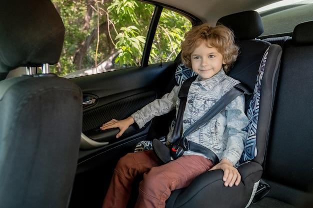 Szczęśliwy śliczny chłopiec w wieku podstawowym w dżinsowej kurtce i brązowych spodniach siedzi na tylnym siedzeniu samochodu przy oknie i czeka na swoich rodziców