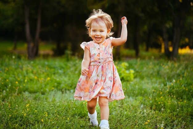 Szczęśliwy śliczny mała dziewczynka bieg na trawie w parku. szczęście.