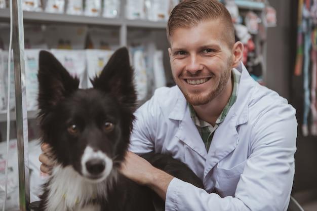 Szczęśliwy śliczny pies patrzeje kamera podczas badania lekarskiego przy weterynarza biurem
