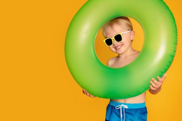 Szczęśliwy słodki chłopiec 6-7 lat w okularach przeciwsłonecznych z boją ratunkową. lato i morze.