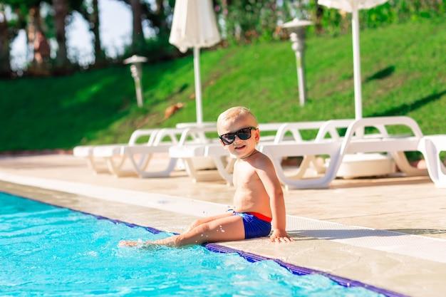 Szczęśliwy słodki chłopiec bawi się na basenie w ośrodku wypoczynkowym