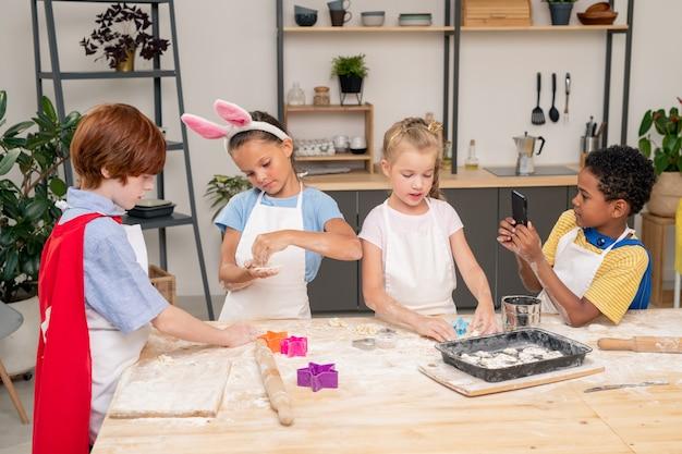 Szczęśliwy słodki chłopiec z surowymi, samodzielnie zrobionymi ciasteczkami, patrząc na ciebie, stojąc przy kuchennym stole przed kamerą