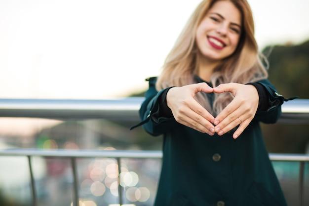 Szczęśliwy słodkie dziewczyny pokazując gest serca z jej palców. miejsce na tekst