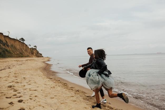 Szczęśliwy ślub para działa i zabawy nad brzegiem morza.