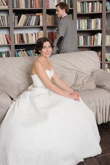 Szczęśliwy ślub para siedzi na kanapie, trzymając się za ręce, czekając na odbiór