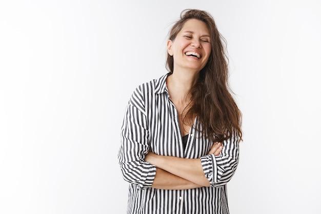 Szczęśliwy śmiech w średnim wieku szczerze zamyka oczy i krzyżuje ręce nad klatką piersiową bawiąc się uroczym prezentem zrobionym przez dzieci, chichocząc radośnie, pozując w pasiastej bluzce na białej ścianie