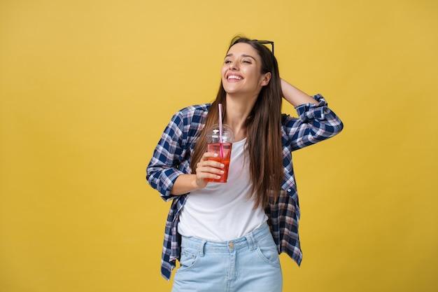 Szczęśliwy śmiejąc się kobieta ubrana w zwykłą szmatkę do picia tropikalnego koktajlu, na białym tle na żółtym tle.
