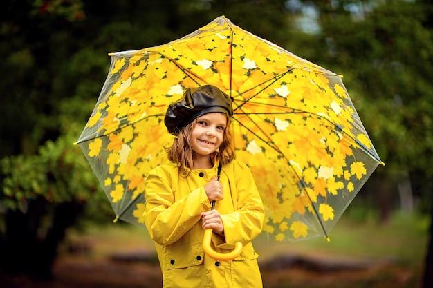 Szczęśliwy śmieszne dziecko dziewczynka z parasolem multicolor w kalosze w parku jesienią.