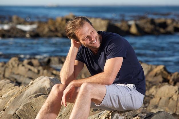 Szczęśliwy sporta mężczyzna obsiadanie outside morzem