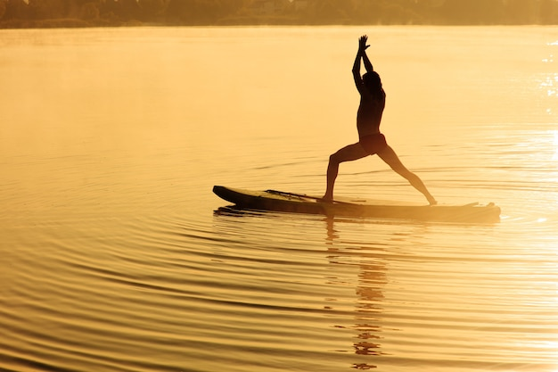 Szczęśliwy sportowiec robi ćwiczenia jogi na pokładzie sup na świeżym powietrzu.