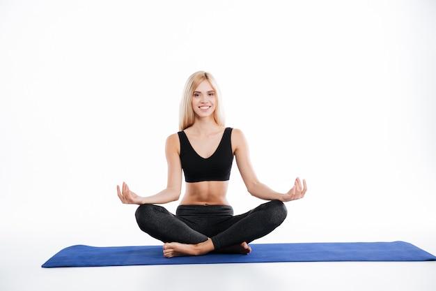 Szczęśliwy sprawności fizycznej kobiety obsiadanie robi ćwiczeniom joga
