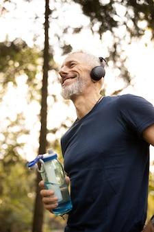 Szczęśliwy sprawny mężczyzna cieszący się treningiem w słonecznym lesie