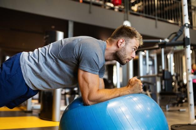 Szczęśliwy sprawny mężczyzna robi ćwiczenia fitness na piłce pilates w siłowni