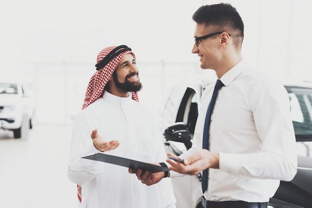 Szczęśliwy sprzedawca klienta trzyma dokumenty wypożyczenia samochodu