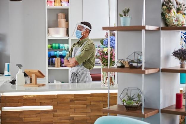 Szczęśliwy sprzedawca stoi przy sterylnym ladzie ze świeżymi bukietami i ma na sobie maskę i szkło ochronne podczas pandemii