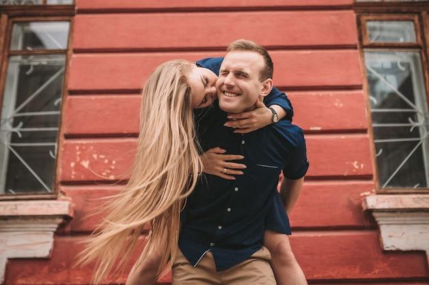 Szczęśliwy stan młodej pary na tle czerwonej ściany, dziewczyna wskoczyła na faceta