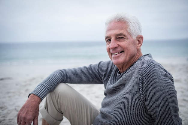 Szczęśliwy starszego mężczyzna obsiadanie na plaży
