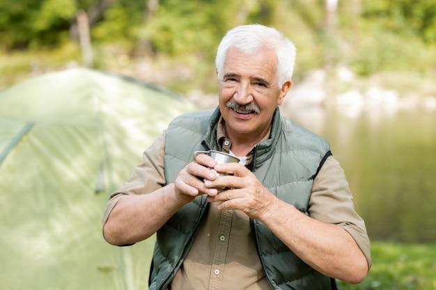 Szczęśliwy starszy aktywny mężczyzna z gorącym napojem, patrząc na ciebie, ciesząc się podróżą w lesie w letni weekend