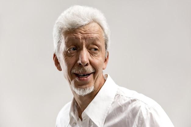 Szczęśliwy starszy biznes człowiek stojący i uśmiechnięty na białym tle na szarym tle studio. piękny portret męski w połowie długości. ludzkie emocje, koncepcja wyrazu twarzy.