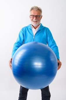 Szczęśliwy starszy brodaty mężczyzna uśmiecha się i stoi, trzymając piłkę gimnastyczną gotowy do siłowni na białym tle