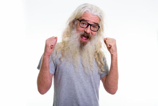 Szczęśliwy starszy brodaty mężczyzna uśmiecha się i szuka podekscytowany