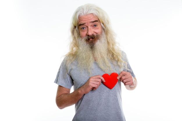 Szczęśliwy starszy brodaty mężczyzna uśmiecha się i trzyma czerwone serce