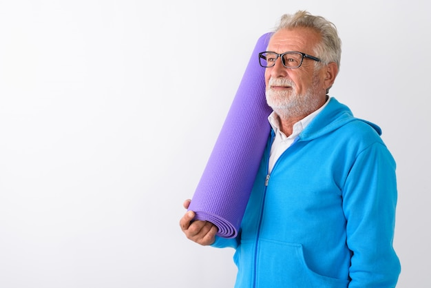Szczęśliwy starszy brodaty mężczyzna uśmiecha się podczas myślenia i trzymając matę do jogi gotowy do siłowni na białym tle