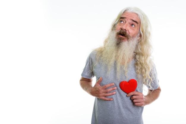 Szczęśliwy starszy brodaty mężczyzna uśmiecha się podczas myślenia