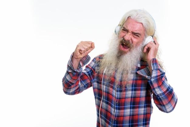 Szczęśliwy starszy brodaty mężczyzna uśmiecha się podczas słuchania