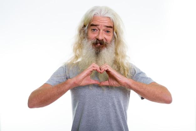 Szczęśliwy starszy brodaty mężczyzna uśmiecha się robiąc znak serca