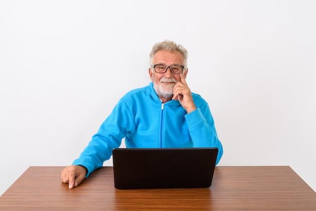 Szczęśliwy starszy brodaty mężczyzna uśmiecha się siedząc z laptopem na drewnianym stole na białym tle