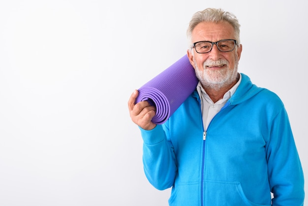 Szczęśliwy starszy brodaty mężczyzna uśmiecha się trzymając matę do jogi gotowy do siłowni na białym tle