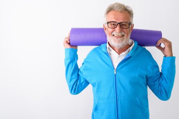 Szczęśliwy starszy brodaty mężczyzna uśmiecha się trzymając matę do jogi za plecami gotowy do siłowni na białym tle