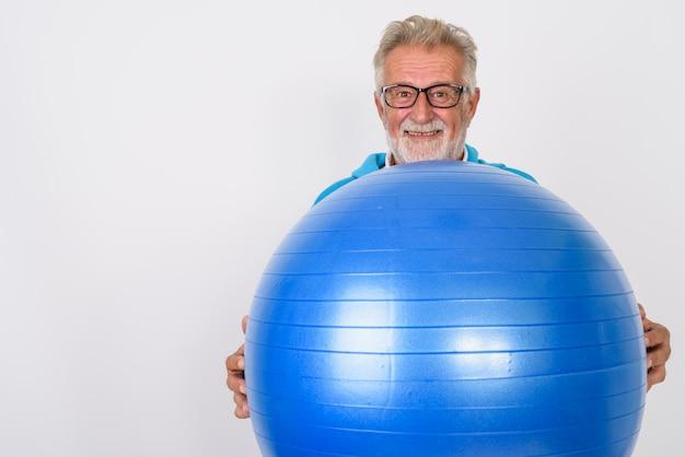Szczęśliwy starszy brodaty mężczyzna uśmiecha się trzymając piłkę gimnastyczną gotowy do siłowni na białym tle