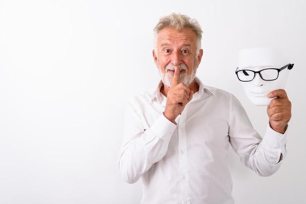 Szczęśliwy starszy brodaty mężczyzna uśmiecha się z palcem na ustach, trzymając białą maskę w okularach na białym tle