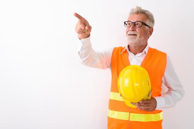 Szczęśliwy starszy brodaty pracownik budowlany uśmiechnięty, wskazując palcem i trzymając kask z okularami na białym tle