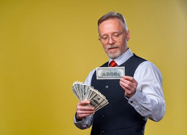 Szczęśliwy starszy człowiek biznesu z fanem banknotów dolarowych na białym tle na żółtym tle. starszy facet wygrał na loterii. szczęśliwy dzień. ludzkie emocje i mimika twarzy