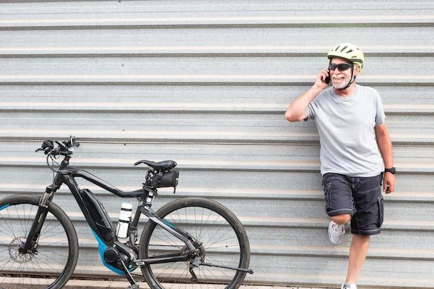 Szczęśliwy starszy człowiek stojący rozmawia przez telefon komórkowy. tło aluminiowe. jeden naród kaukaski. korzystanie z e-roweru z kaskiem