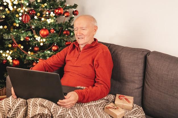 Szczęśliwy starszy kaukaski mężczyzna z laptopem siedzi na kanapie obok choinki z kubkiem herbaty na czacie z rodziną w internecie. samoizolacja, wakacyjny nastrój. pudełka na prezenty.