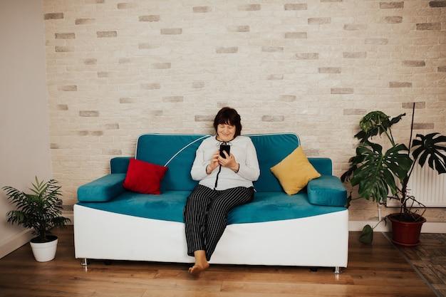 Szczęśliwy starszy kobieta siedzi na niebieskiej kanapie używa telefonu do połączenia wideo